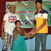 Caregiver Muthu gives prize to child Subramani; behind is Sir Henry in his drama costume
