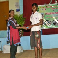 Caregiver Thersa giving prize to Mani